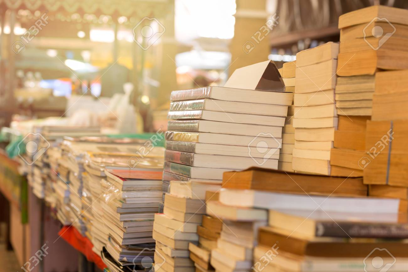 Piles of old books on a table in a market - 94505755