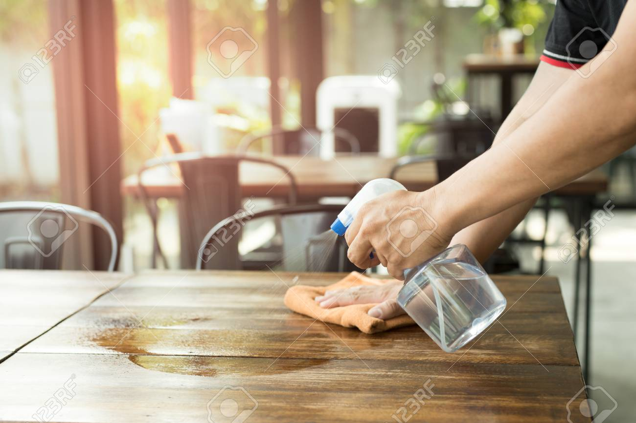 Waiter cleaning the table with Disinfectant Spray in a restaurant - 94528490