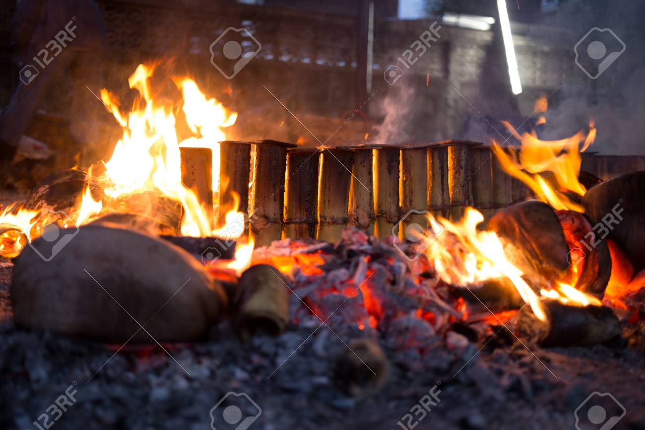 Fire burning on spathe coconut cooking glutinous rice roasted in bamboo shot in low light Stock & Fire Burning On Spathe Coconut Cooking Glutinous Rice Roasted ...