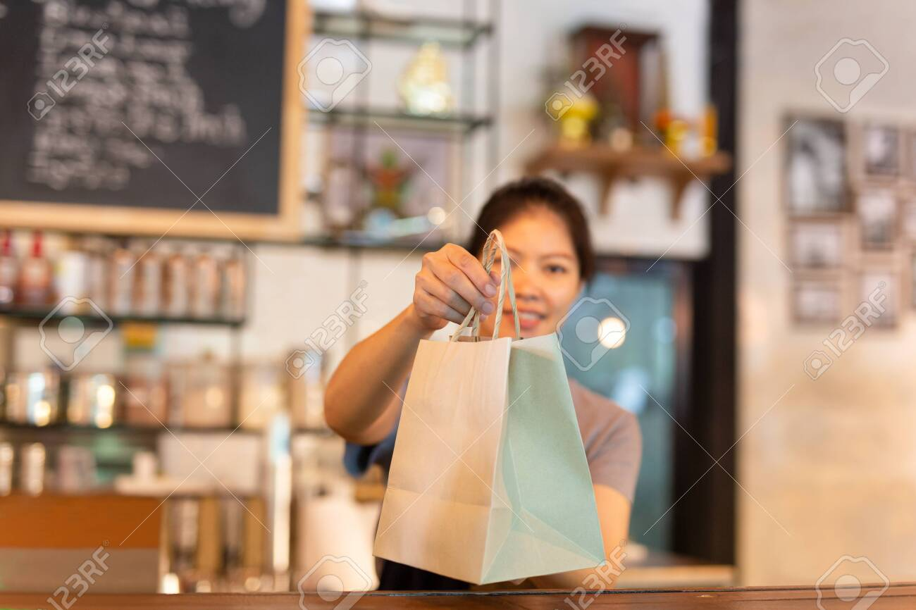 Waitress at counter giving eco friendly paper bag with take away drink in cafe. - 124748536