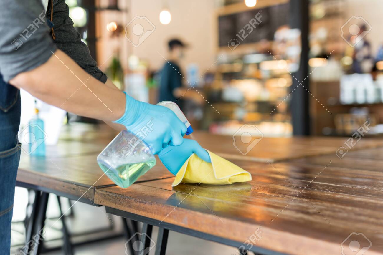 Waiter cleaning the table with disinfectant spray and microfiber cloth in cafe. - 143489088
