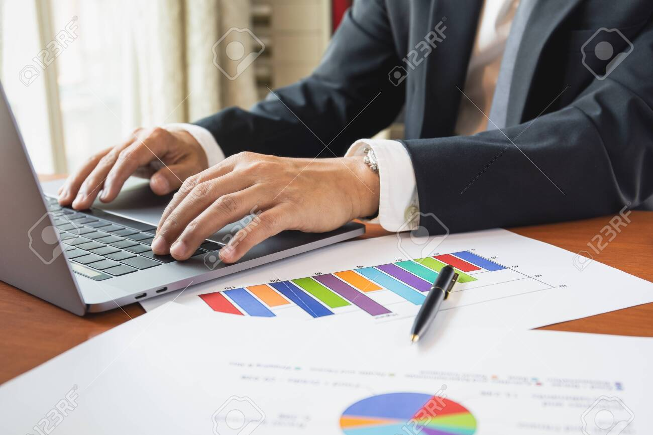 Businessman working on laptop with graph stock chart on table. - 144589128