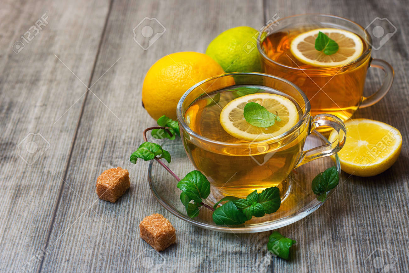 Two Glass tea Cup's with lemon, lime and mint on gray wooden background. - 166379173