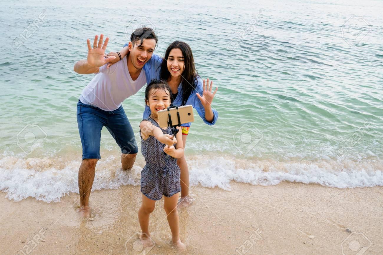 Portrait of happy family, taking selfie on beach Stock Photo - 103175776