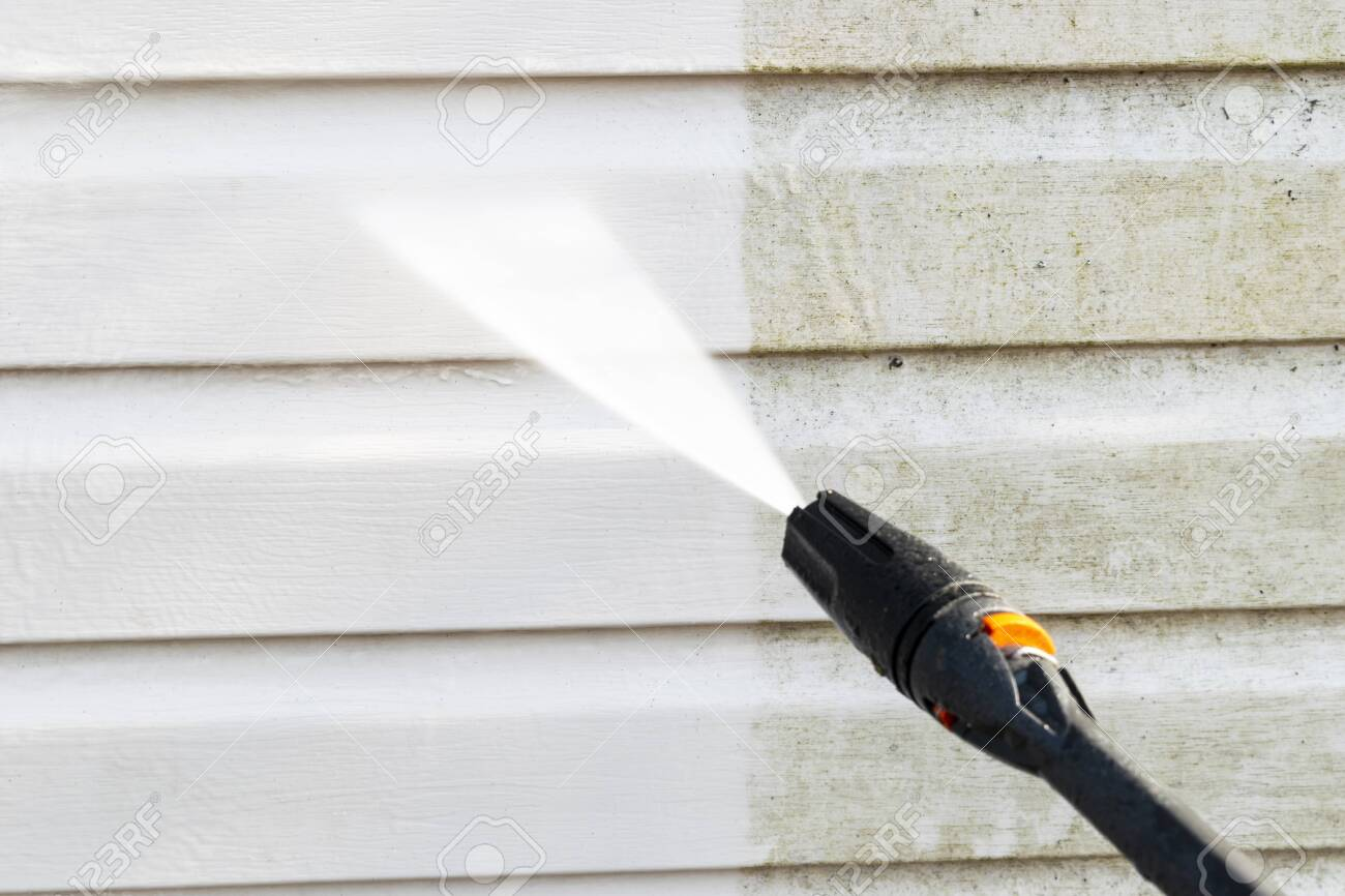 Cleaning service washing building facade with pressure water. Cleaning dirty wall with high pressure water jet. Power washing the wall. Cleaning the facade of the house. Before and after washing - 121954582