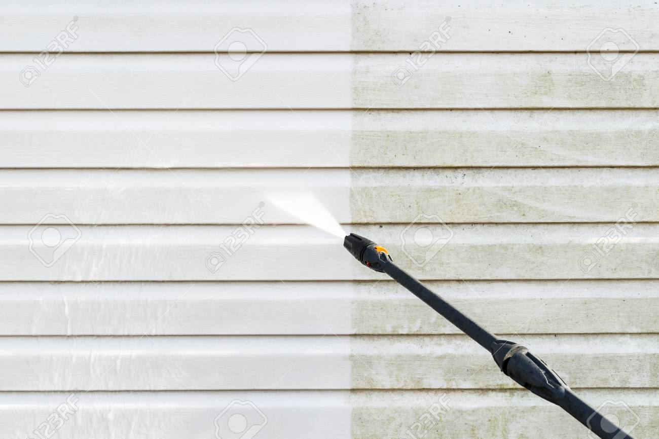 Cleaning service washing building facade with pressure water. Cleaning dirty wall with high pressure water jet. Power washing the wall. Cleaning the facade of the house. Before and after washing - 121954589