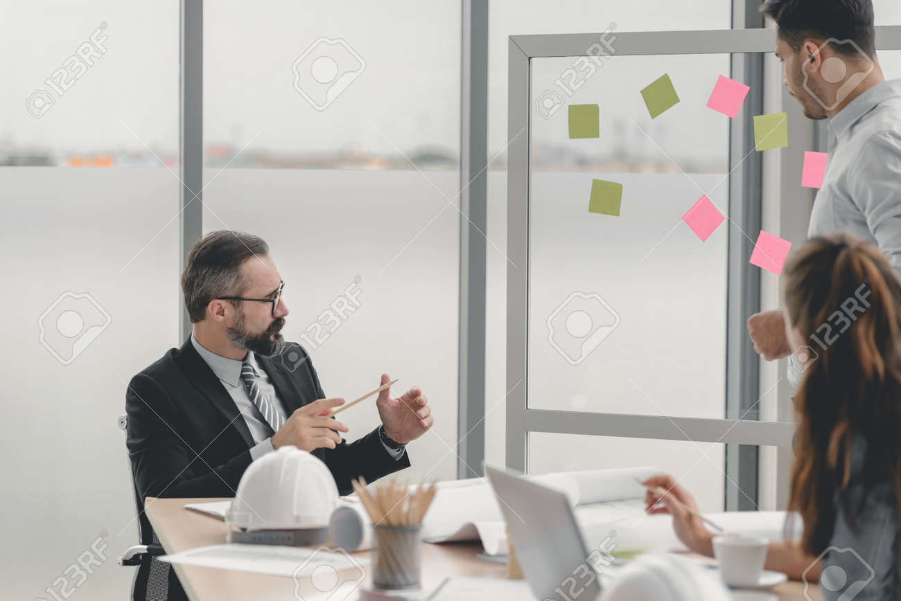 Engineers team meeting for architectural project. architects discussing blueprint with construction manager in office worker conference site. Construction Concept - 157100419