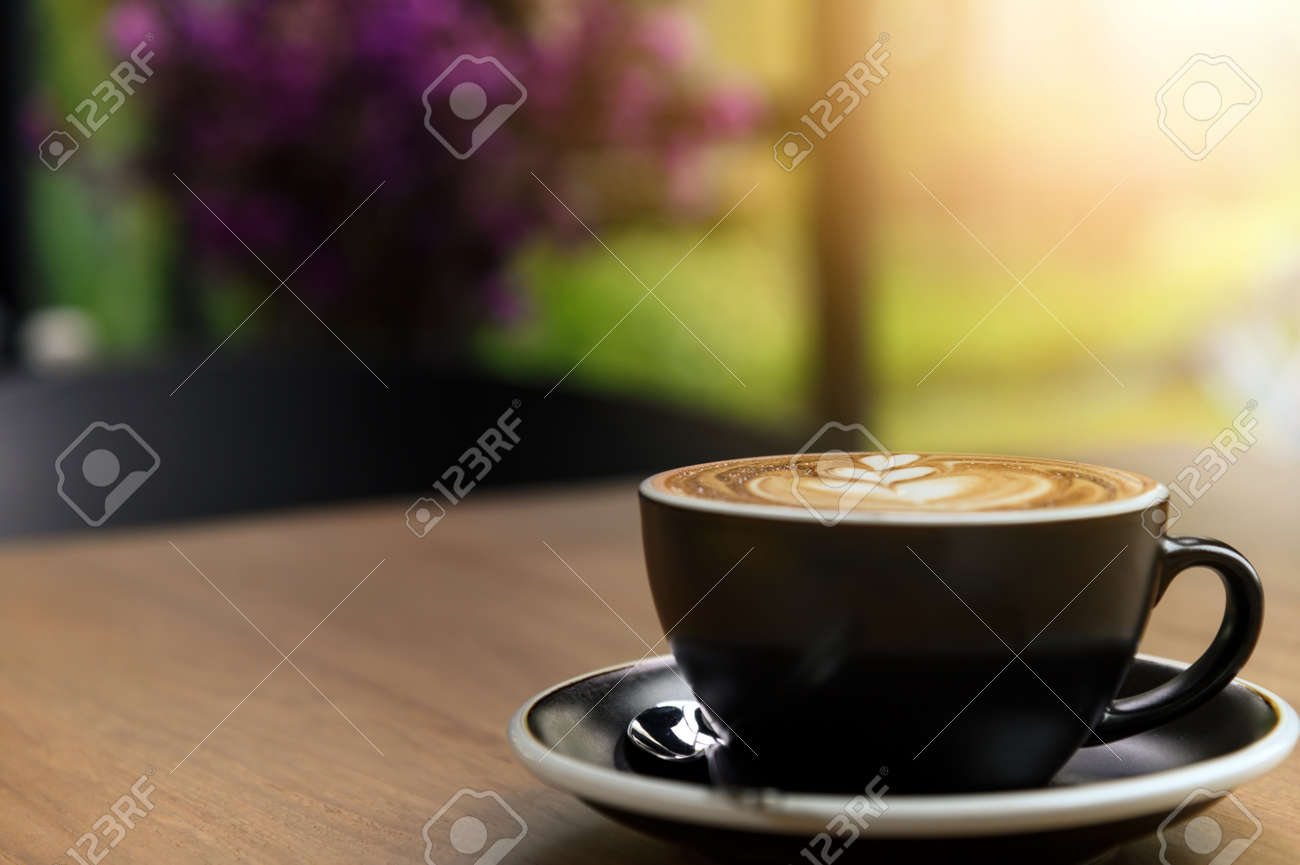 Nice cup of fresh brewed coffee with beautiful latte art on wooden table in cafe with copy space. Coffee break recreation relaxation - 165342478