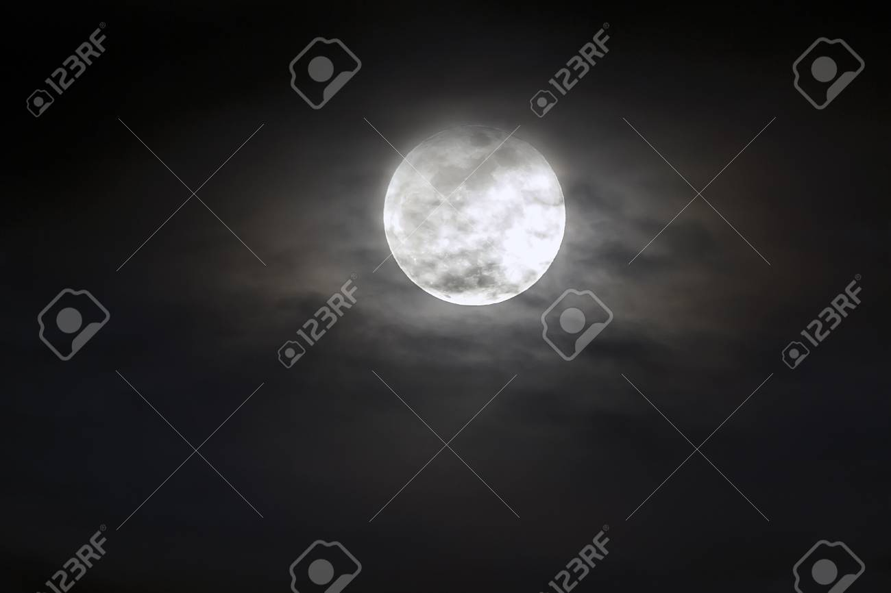 Big silver glowing Moon close-up on dark blue sky with scattered clouds. - 96084646