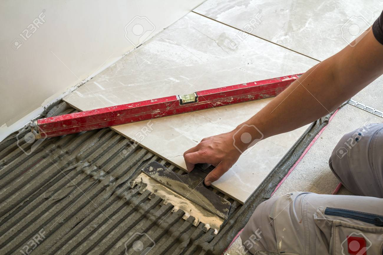 Ceramic Tiles And Tools For Tiler Worker Hand Installing Floor