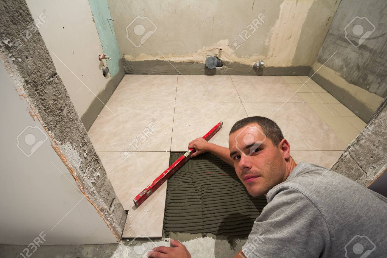 Home tiles improvement handyman with level laying down tile home tiles improvement handyman with level laying down tile floor renovation and construction concept dailygadgetfo Choice Image
