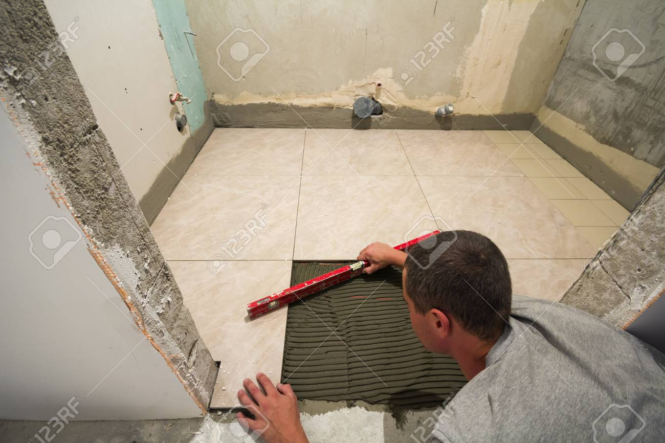 Home Tiles Improvement Handyman With Level Laying Down Tile