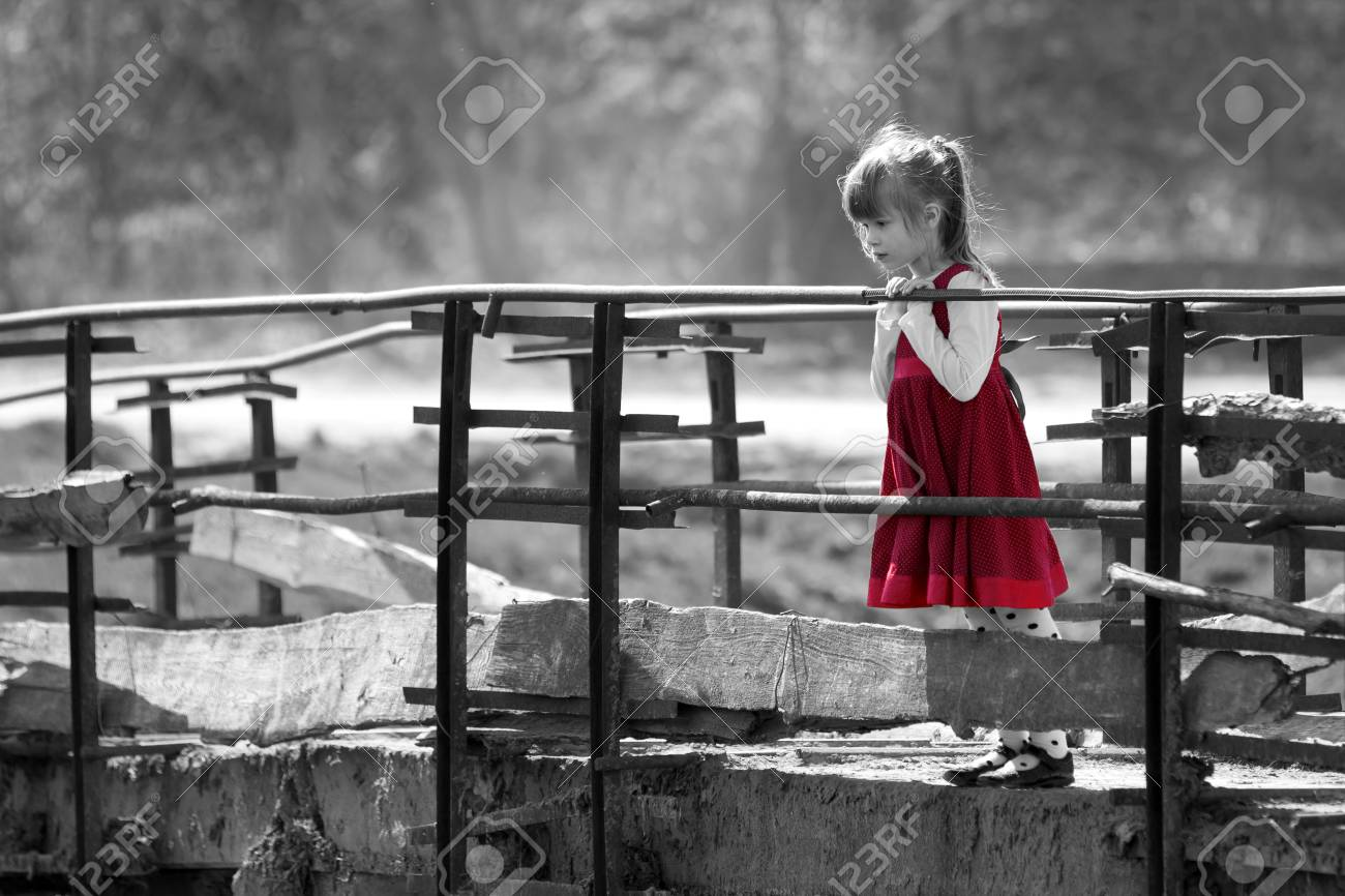 Black and white picture of pretty blond child girl in red dress