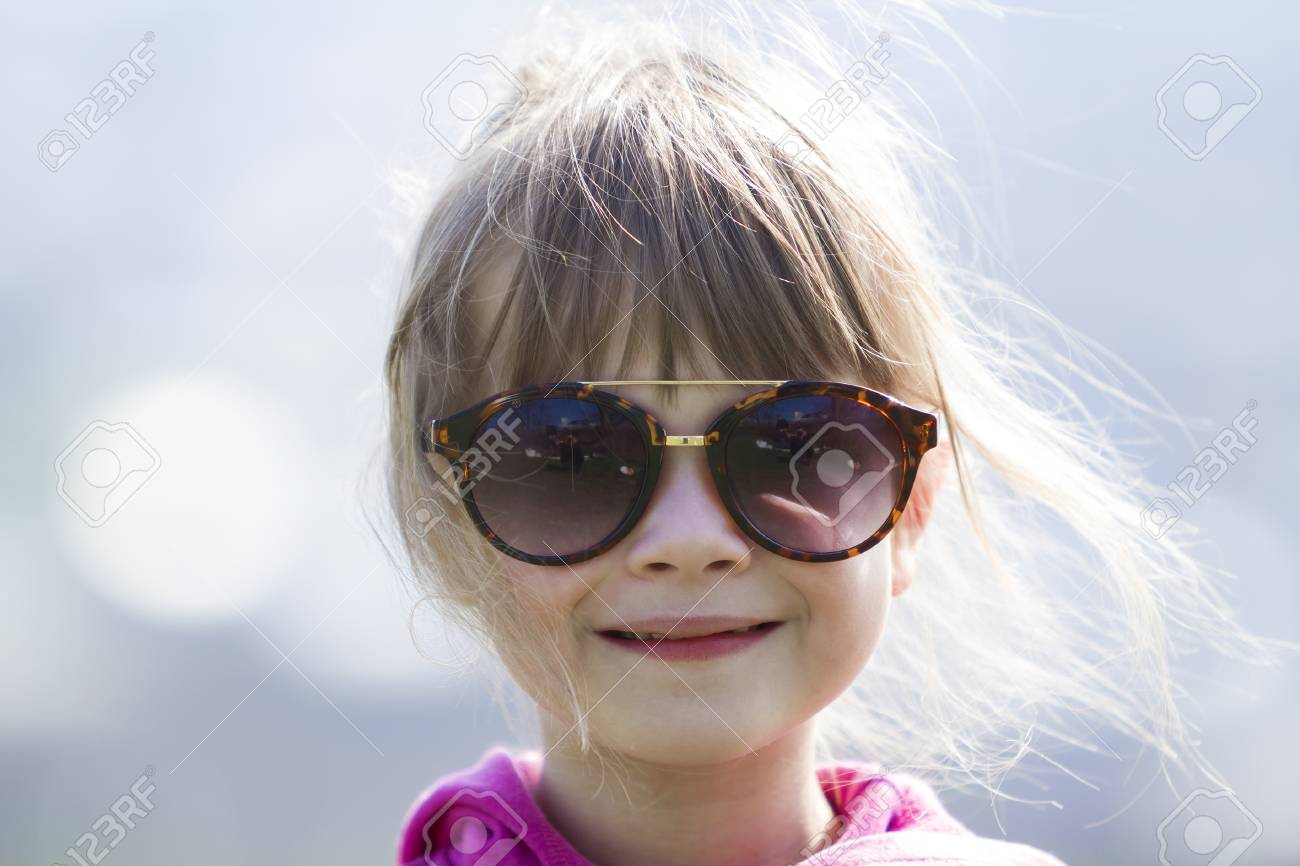 4cf2f86faa2d Portrait of cute pretty little blond preschool girl in pink sweater and  dark sunglasses smiling happily