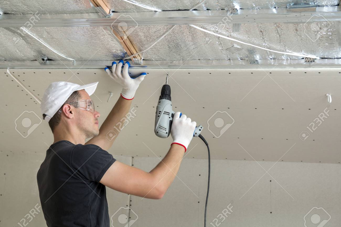 Young man in goggles fixing drywall suspended ceiling to metal
