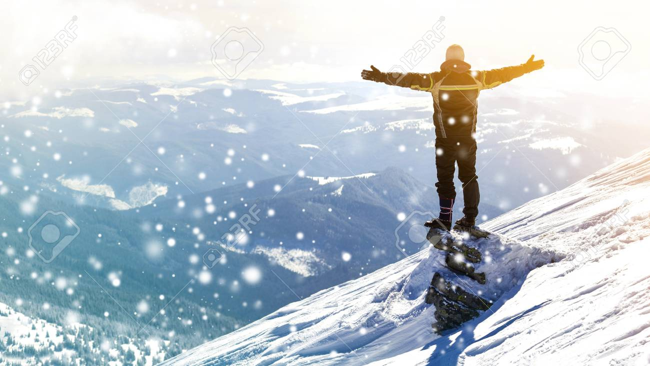 Silhouette of alone tourist standing on snowy mountain top in winner pose with raised hands enjoying view and achievement on bright sunny winter day. Adventure, outdoors activities, healthy lifestyle. - 110470587