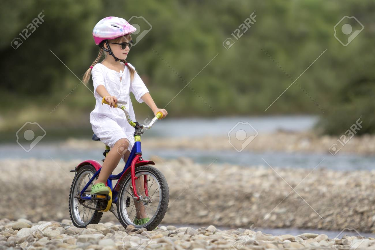 e33f6885bcdc Cute young girl in white clothing, sunglasses with long braids wearing pink  safety helmet riding