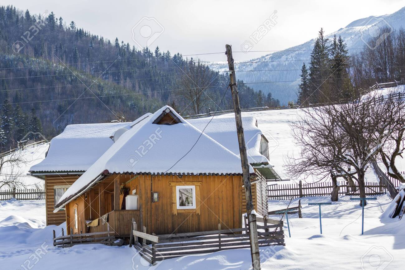Beautiful cozy one-story wooden ecological comfortable traditional residential cottage houses with terrace, attic room and steep roof covered with snow on mountain slope on sunny cold winter day. - 126267334