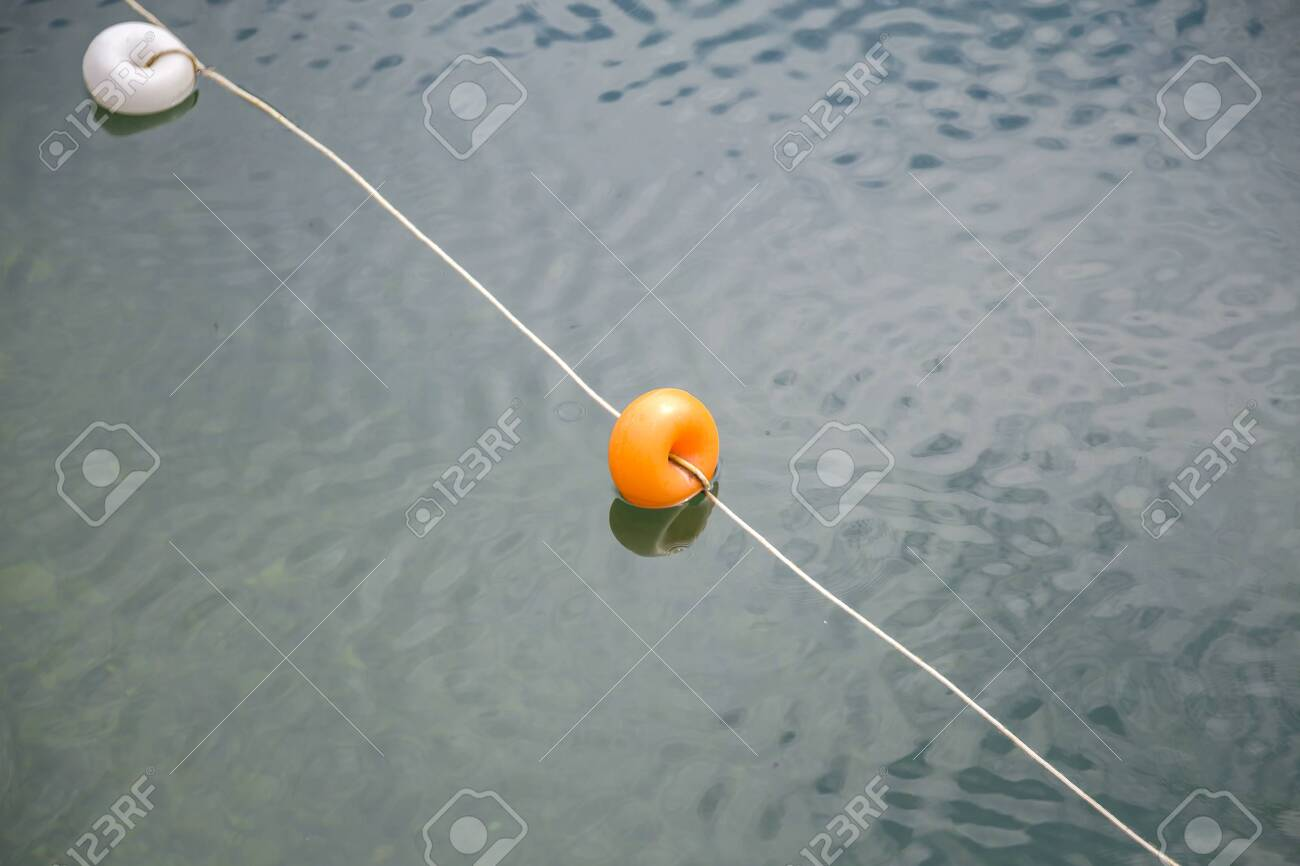 Rope with white and yellow restriction markers on water surface for prohibiting of swimming in deep lake or sea. - 134715406