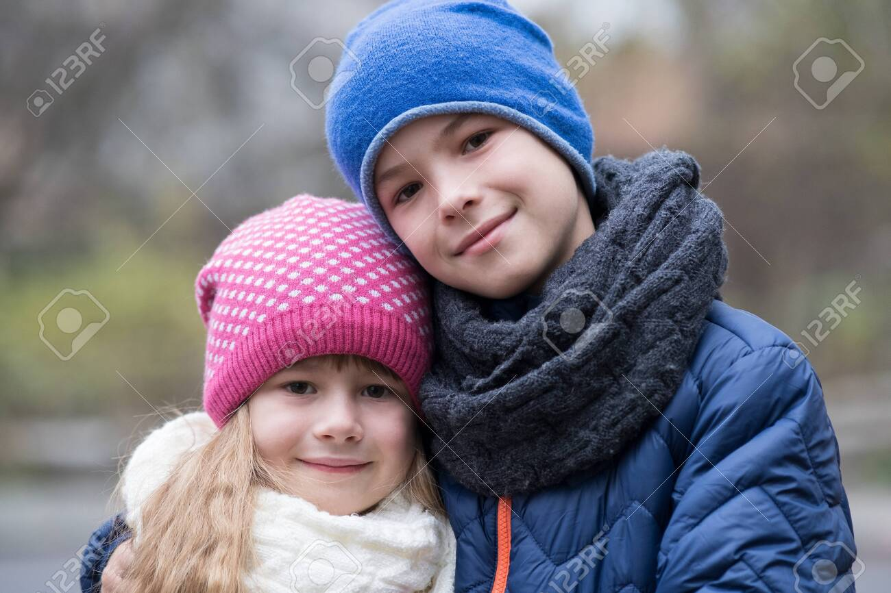 Two children boy and girl hugging each other outdoors wearing warm clothes in cold autumn or winter weather. - 135005933