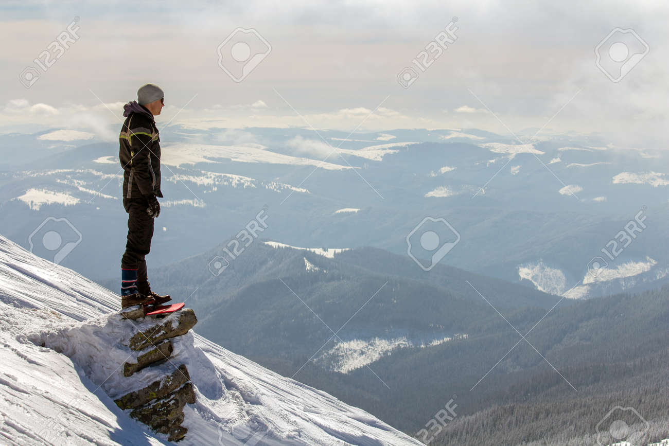 Silhouette of alone tourist standing on snowy mountain top enjoying view and achievement on bright sunny winter day. Adventure, outdoors activities and healthy lifestyle concept. - 135229500