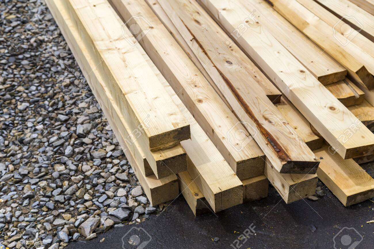 Stack of natural wooden boards on building site. Industrial timber for carpentry, building or repairing, lumber material for roofing construction. - 142777717