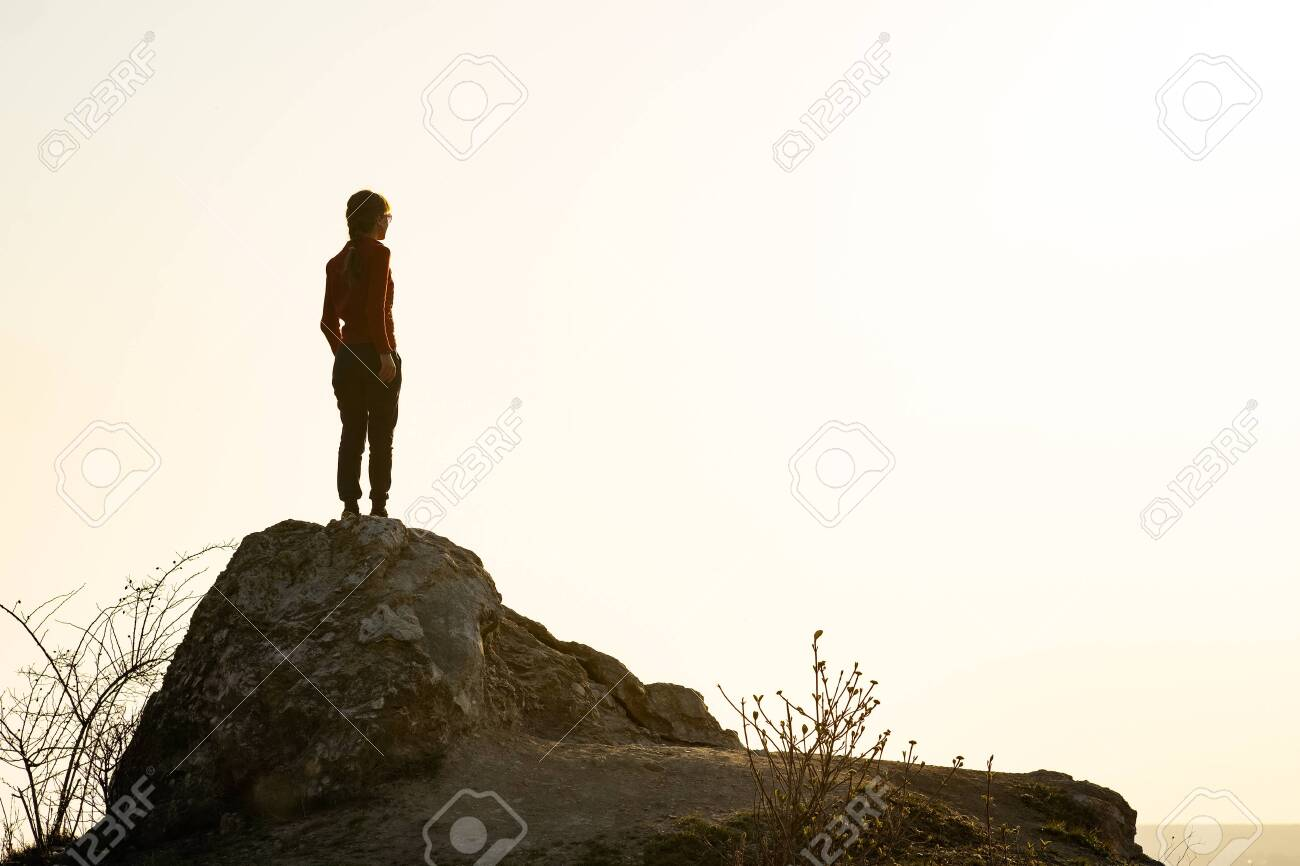 Young woman hiker standing alone on big stone in morning mountains. Female tourist on high rock in wild nature. Tourism, traveling and healthy lifestyle concept. - 145334988