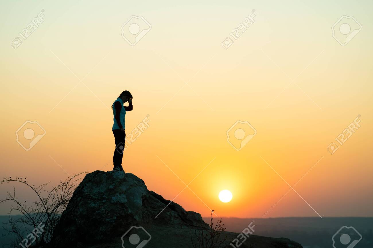 Silhouette of a woman hiker standing alone on big stone at sunset in mountains. Female tourist on high rock in evening nature. Tourism, traveling and healthy lifestyle concept. - 149773646