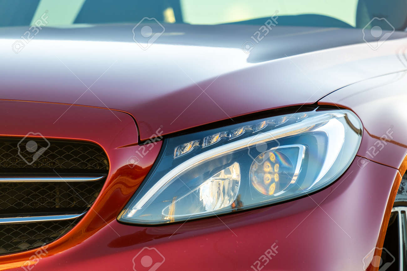 Closeup of front headlight of new clean car parked on a city street side. - 165134596
