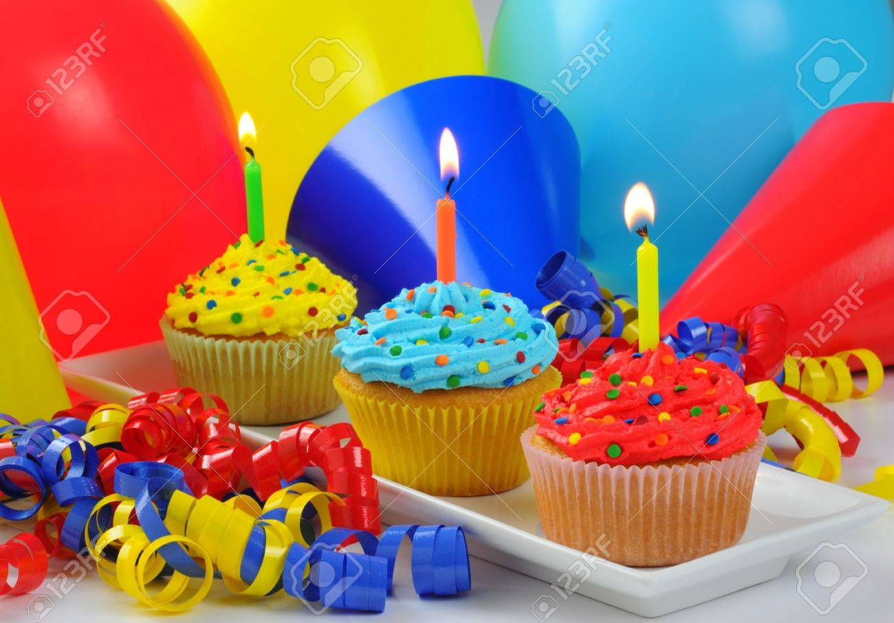 Colorful Birthday Cupcakes With Lit Candles Stock Photo