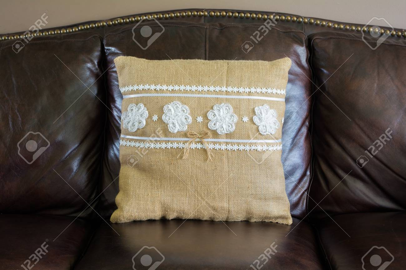 Canapé En Toile De Jute un oreiller de toile de jute avec de la dentelle blanche sur un canapé en  cuir