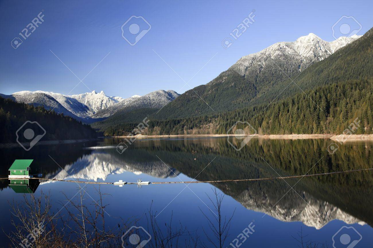 Capilano Reservoir Lake Long Reflection Green Building Dam Snowy Two Lions Snow Mountains Vancouver British Columbia Pacific Northwest Stock Photo - 10182015