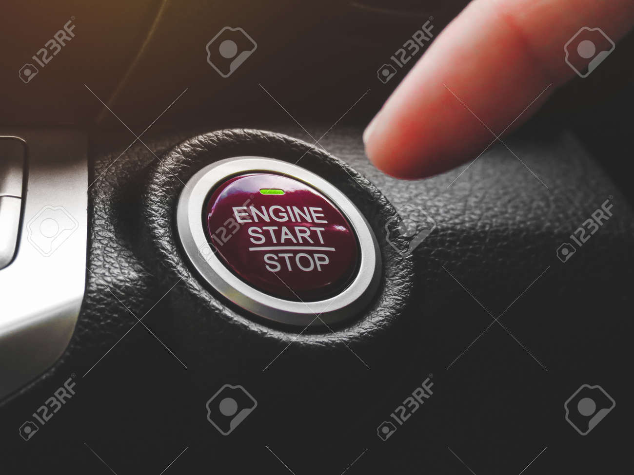 Car driver press to the engine start stop button for engine ignition in a luxury car - 154314254