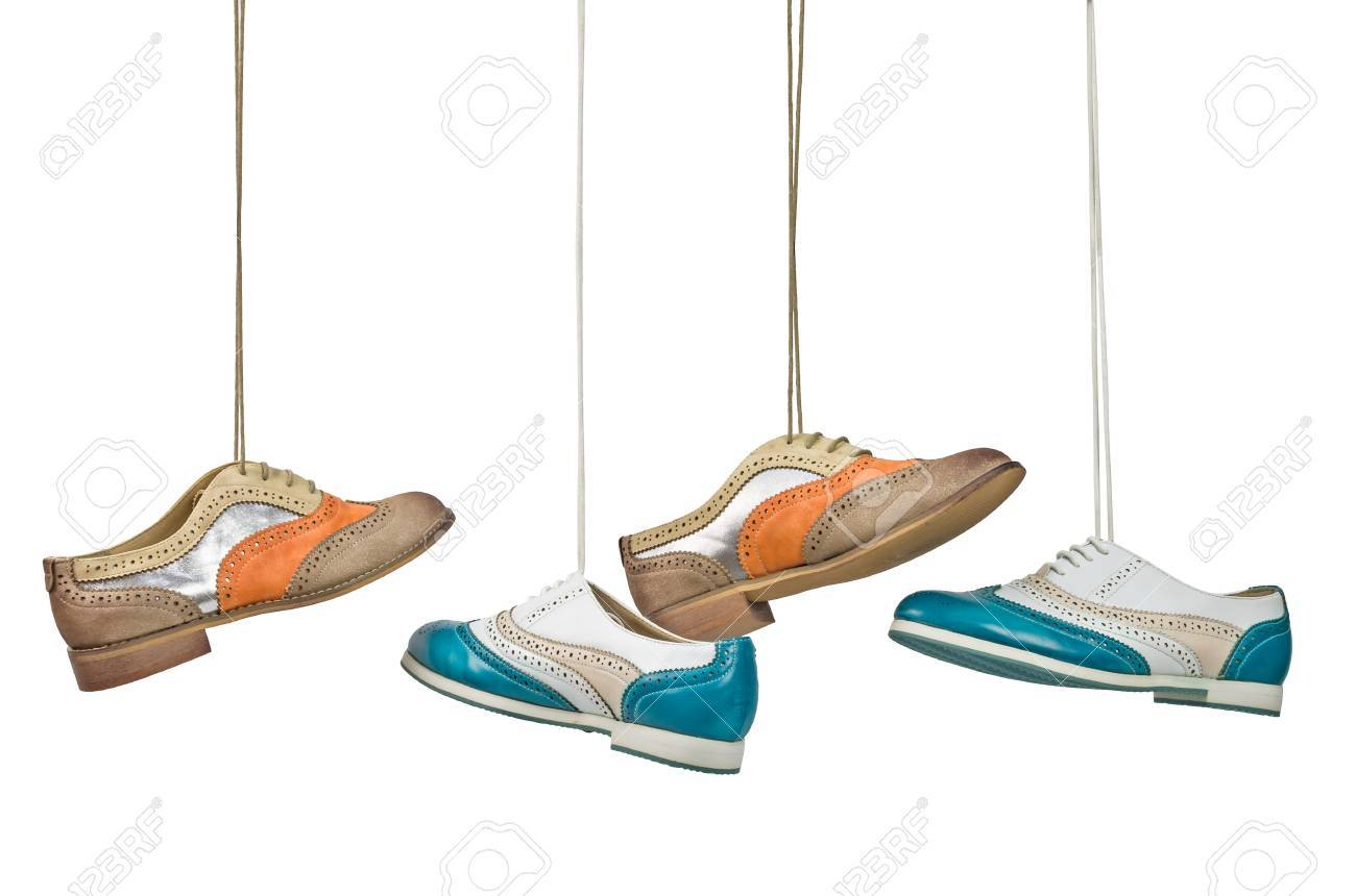 Nice woman color shoes hanging on laces on isolated white background