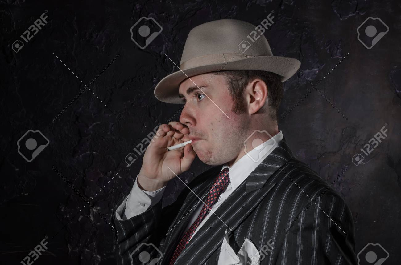 Private detective in old fashion hat smokes a cigarette. Gangster looks like  mafiosi and stay 48ad953a3ce