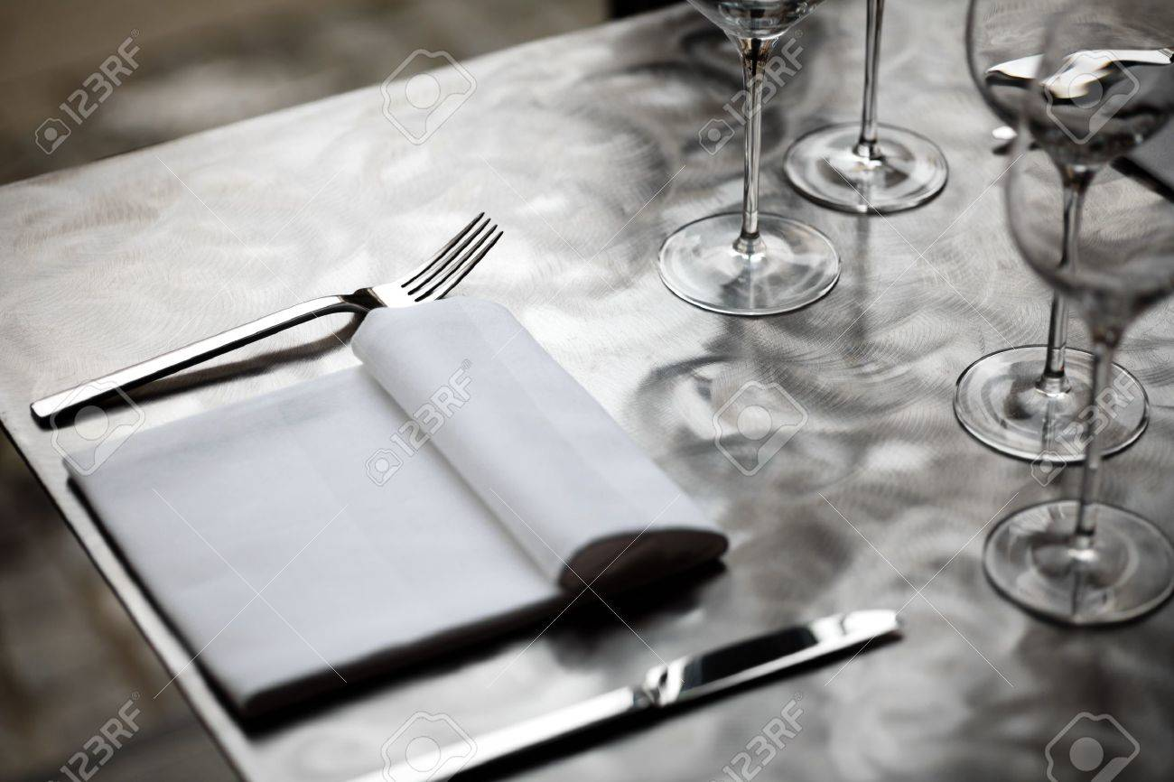 Fancy Restaurant Table Setting - Fine restaurant dinner table place setting with napkin and wineglass stock photo 18134746