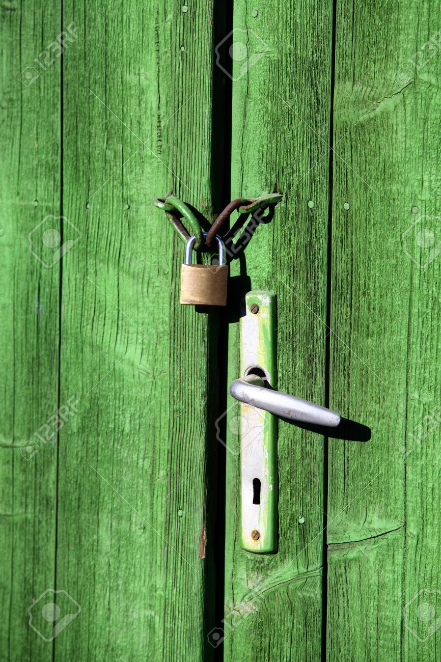 Color Shot Of A Vintage Door Handle And A Lock On A Wooden Green