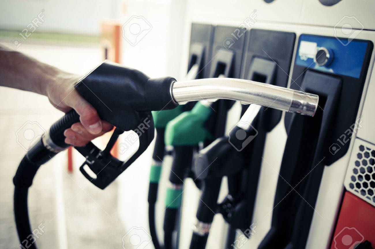 Detail of a hand holding a fuel pump at a station - 52676686