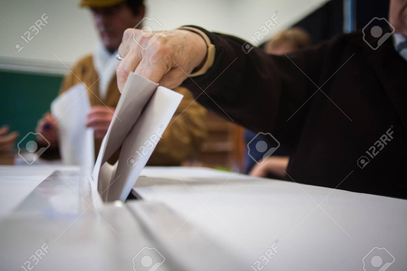 Bureaux De Vote Pour Les Legislatives : Une personne dépose son bulletin de vote lors du vote pour les