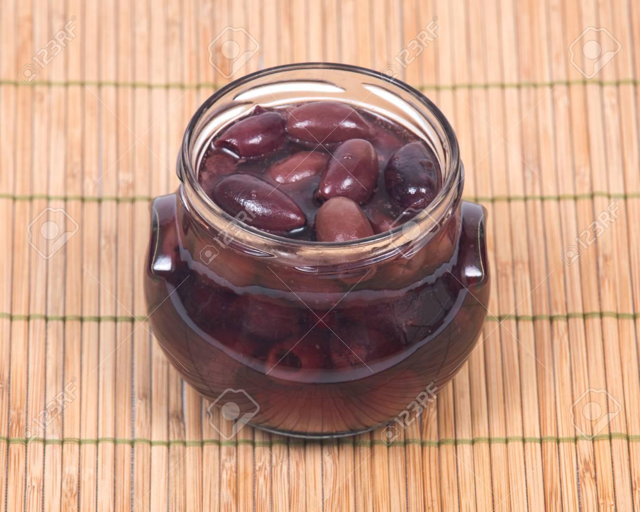 Jumbo Pitted Kalamata Oliven Im Glas Auf Bambus Tischset Lizenzfreie