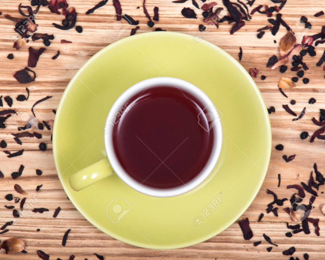 Wild Berry Tea In Green Cup With Hibiscus Leafs On Wooden Vintage