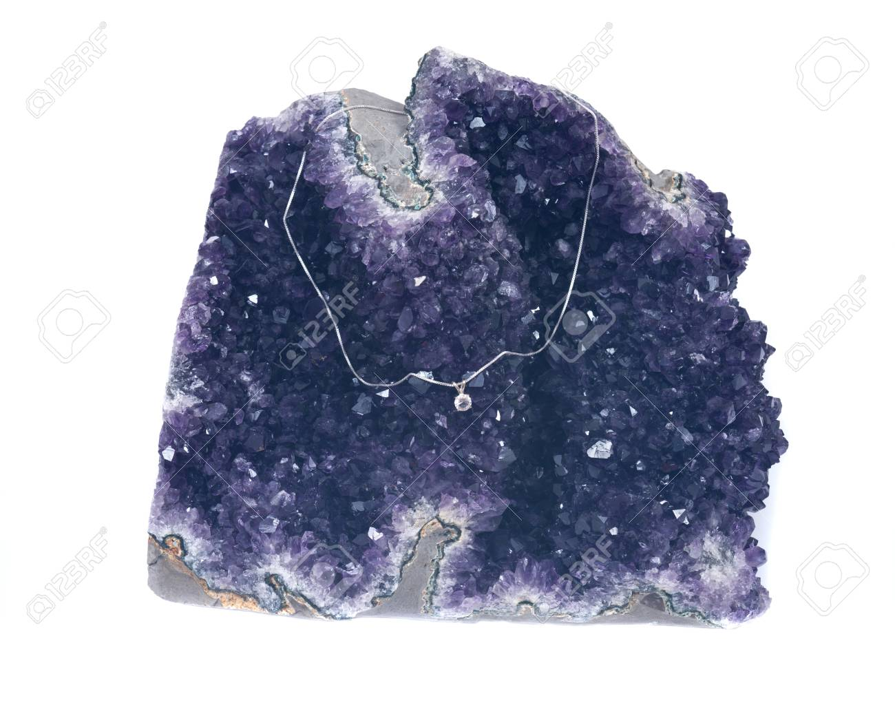 Crystal pendant on silver chain presented on amethyst geode isolated