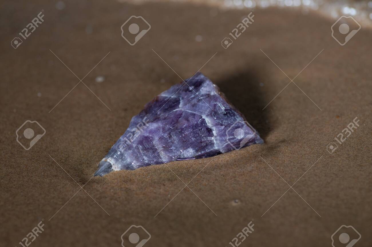 High grade rough natural Purple Auralite 23 Amethyst point from Canada on wet sand in front of the lake at sunrise. - 128873659