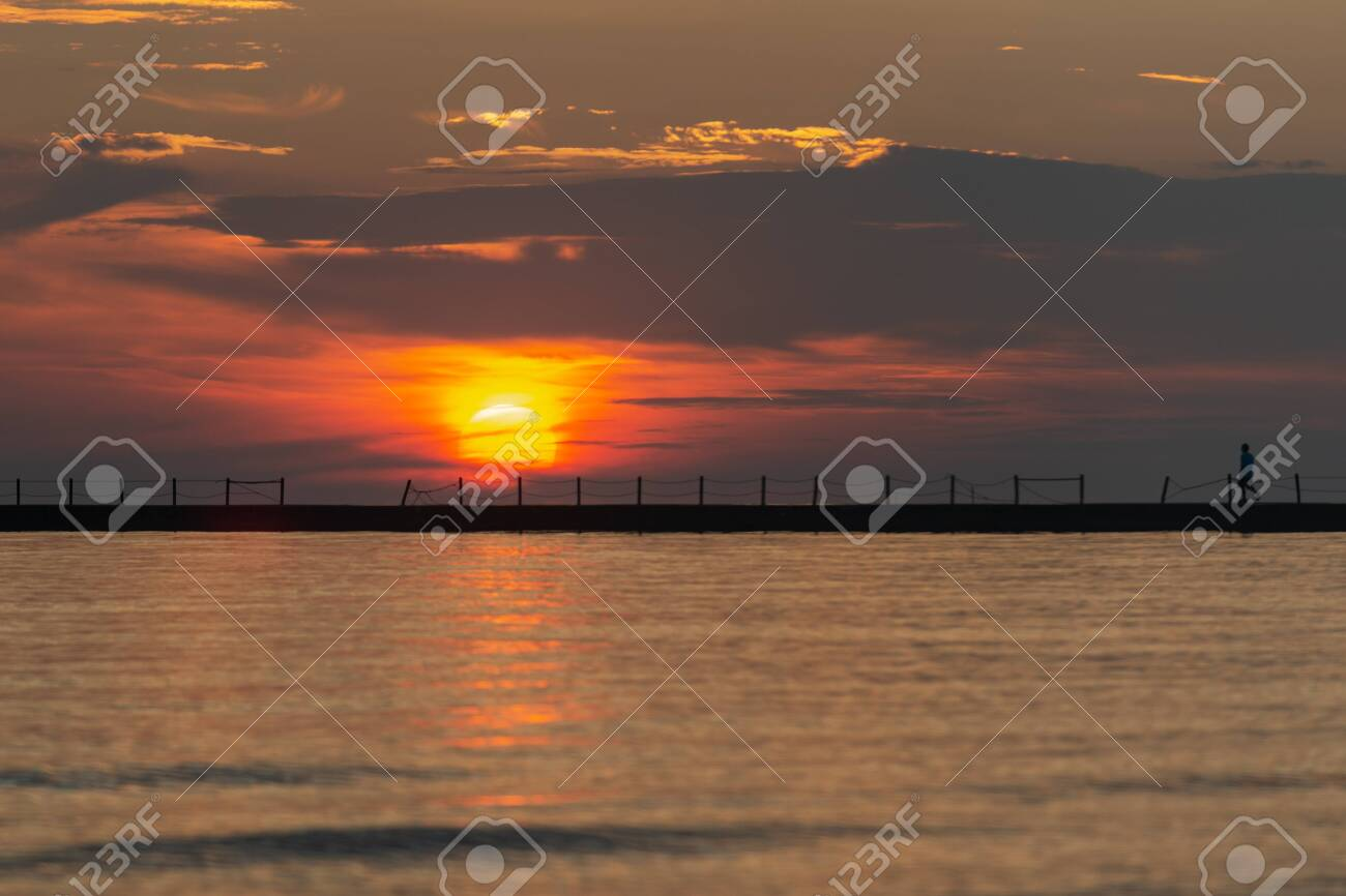 Silhouette of a walking man at a Pier at Sunrise with Sun reflecting in the Lake Michigan. - 128873684