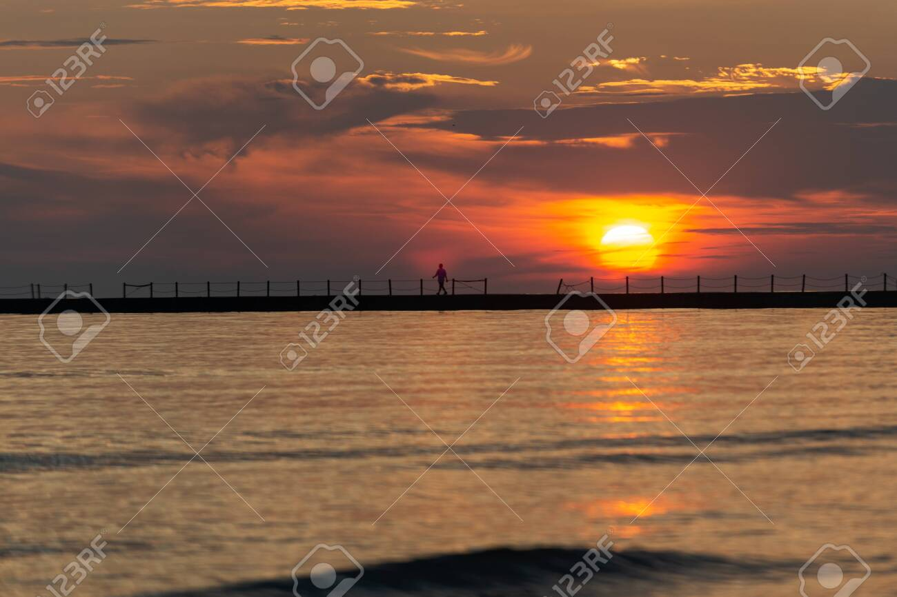 Silhouette of a walking man at a Pier at Sunrise with Sun reflecting in the Lake Michigan. - 128873682