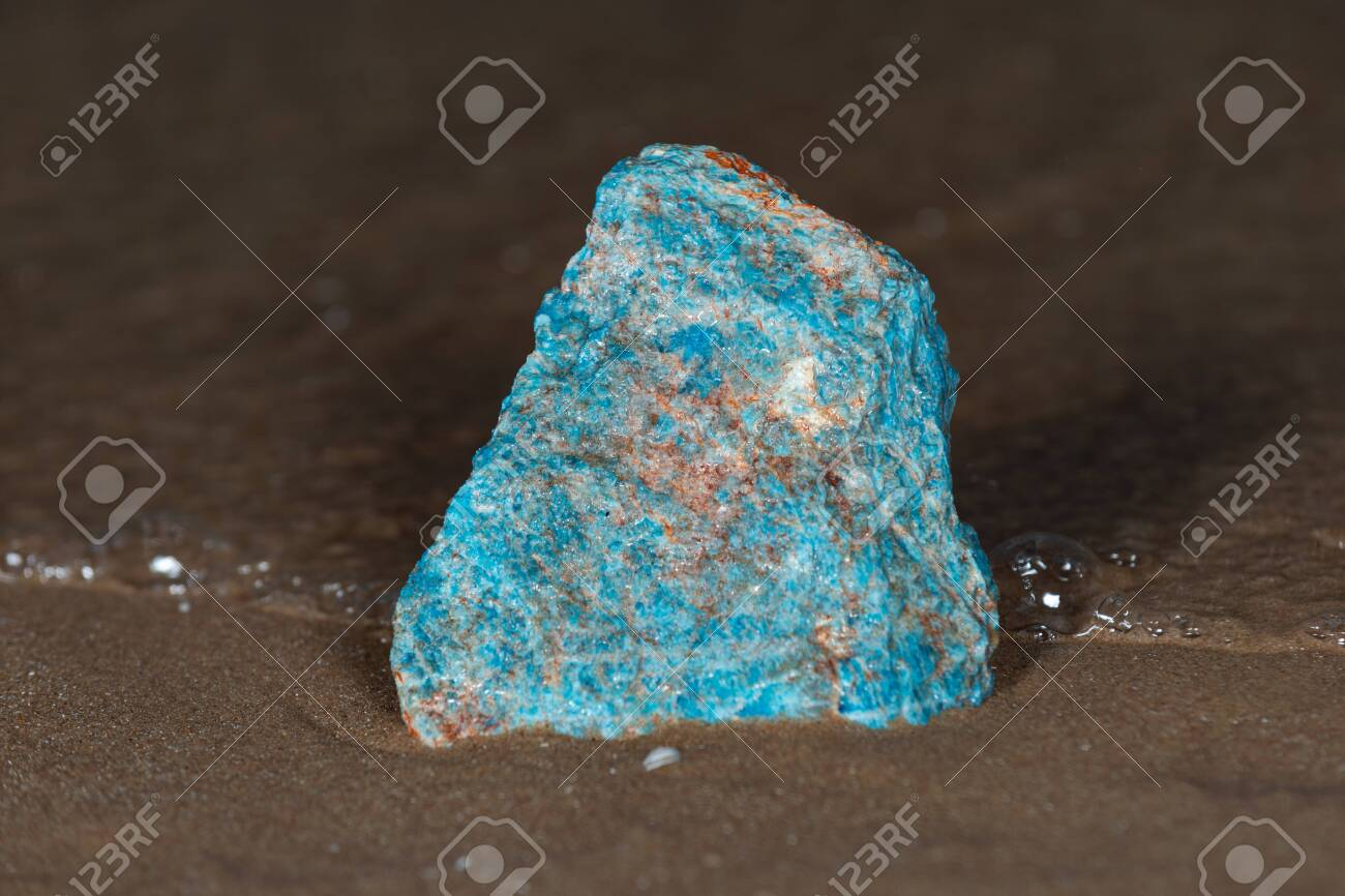 High grade rough natural Blue Apatite Specimen from Madagascar on wet sand in front of the lake at sunrise. - 128873681