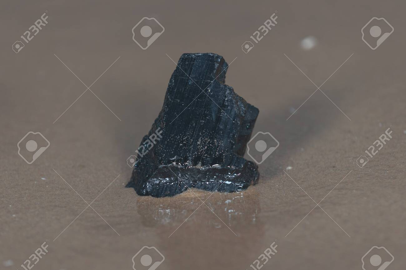 Extra Grade Black Tourmaline chunk from Brazil on wet sand on the beach at sunrise in front of the lake. - 128873624