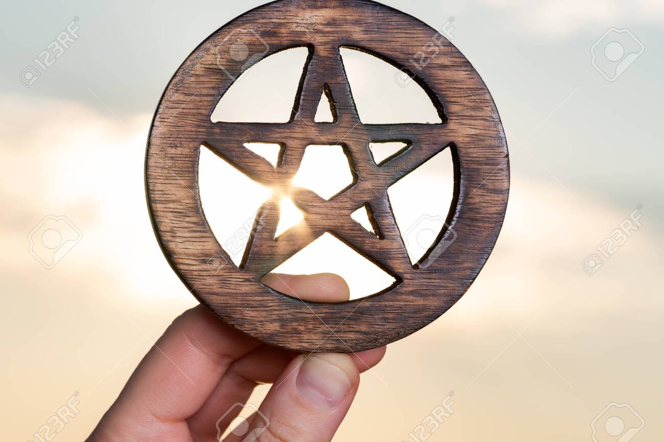 Woman's hand holding Wooden encircled Pentagram symbol at sunrise in front of the lake. Concept of Five elements: Earth, Water, Air, Fire, Spirit. - 128873643