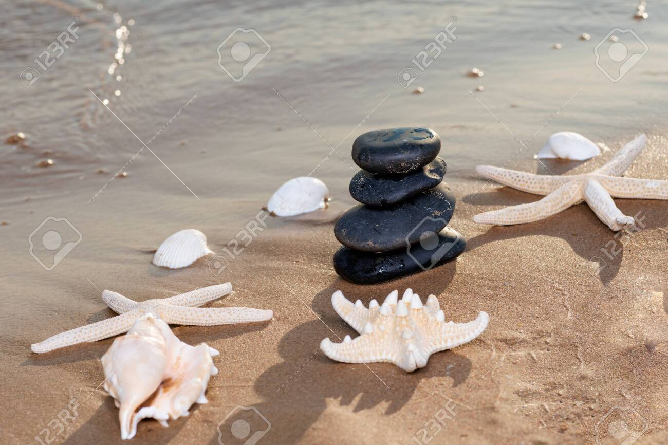 Spa composition - stacked Basalt Stones, Seashells and Sea Stars on the beach at sunrise in front of the ocean. Wellness, Balance and Relax concept. - 128873551