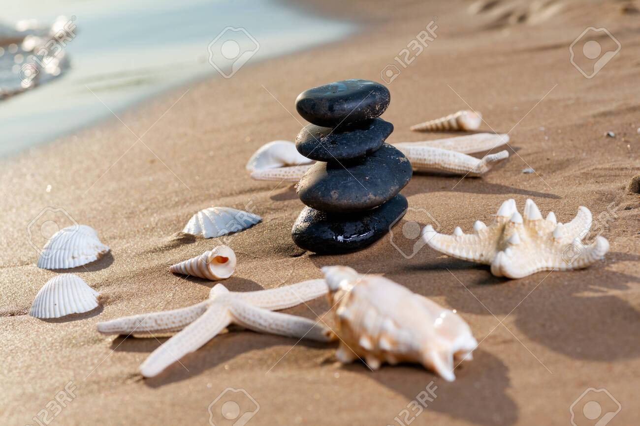 Spa composition - stacked Basalt Stones, Seashells and Sea Stars on the beach at sunrise in front of the ocean. Wellness, Balance and Relax concept. - 128873546